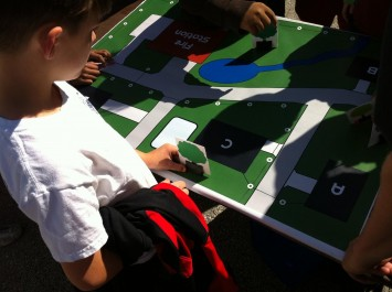 Photo 2: Students at Columbia's Lee Elementary School place trees onto the community map at Lee's 2014 Arbor Day celebration. By hosting this activity outdoors, students could see the real-life shading effect of trees on homes.