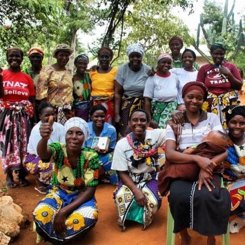 Photo 1: The Tumaini women's group poses after receiving their solar lamps on credit.