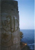 """Façade of tower overlooking former slave market on Île de Gorée (Senegal), now preserved by UNESCO as a """"memory island"""" for intercultural dialogue and reconciliation. Graffiti spells Allahu Akbar. Photo by Adrian Fielder (2000)"""