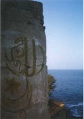 "Façade of tower overlooking former slave market on Île de Gorée (Senegal), now preserved by UNESCO as a ""memory island"" for intercultural dialogue and reconciliation. Graffiti spells Allahu Akbar. Photo by Adrian Fielder (2000)"