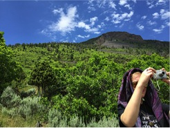 A student taking a photo during the Basalt Mountain hike led by Jerome
