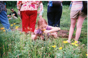 Figure 10: A child smells the flowers at Zydeco Moon Farm. Photo by visitor.
